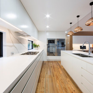 Photo of a large contemporary l-shaped eat-in kitchen in Canberra - Queanbeyan with flat-panel cabinets, white cabinets, white splashback, stainless steel appliances, with island, brown floor, an undermount sink, window splashback and medium hardwood floors.