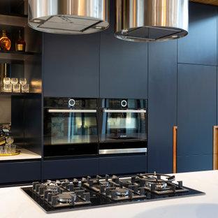 Diseño de cocina de galera, minimalista, grande, abierta, con fregadero bajoencimera, puertas de armario azules, encimera de cuarzo compacto, electrodomésticos negros, suelo de baldosas de porcelana, una isla, suelo gris y encimeras blancas