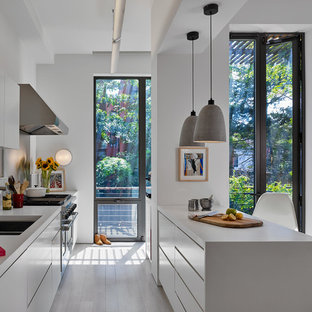 Mid-sized contemporary kitchen pictures - Inspiration for a mid-sized contemporary galley painted wood floor and white floor kitchen remodel in New York with an undermount sink, flat-panel cabinets, white cabinets, stainless steel appliances, an island, white countertops and gray backsplash