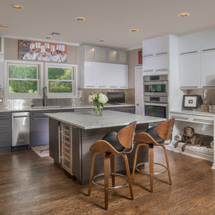 Large contemporary kitchen remodeling - Example of a large trendy u-shaped dark wood floor and brown floor kitchen design in Other with an undermount sink, flat-panel cabinets, gray cabinets, metallic backsplash, stainless steel appliances, an island and subway tile backsplash