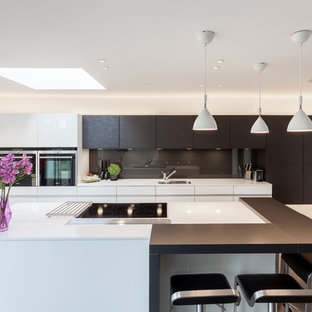 Contemporary kitchen in Glasgow with a single-bowl sink, flat-panel cabinets, brown cabinets, brown splashback, glass sheet splashback, an island and white worktops.