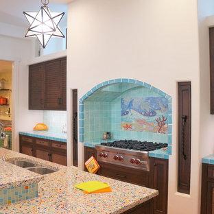 Esempio di una grande cucina costiera con lavello sottopiano, ante a persiana, ante marroni, top in vetro riciclato, paraspruzzi blu, paraspruzzi con piastrelle a mosaico, elettrodomestici in acciaio inossidabile, pavimento in terracotta, isola e pavimento arancione