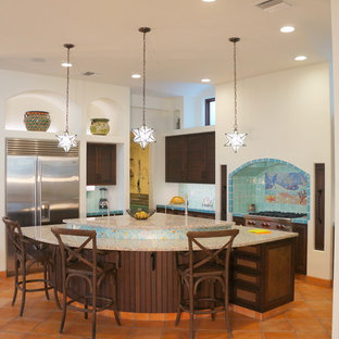 Inspiration for a large mediterranean u-shaped eat-in kitchen in Tampa with an undermount sink, louvered cabinets, brown cabinets, recycled glass benchtops, blue splashback, mosaic tile splashback, stainless steel appliances, terra-cotta floors, with island and orange floor.