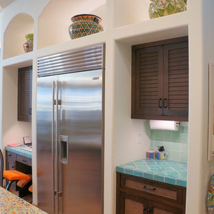 This is an example of a large mediterranean u-shaped eat-in kitchen in Tampa with an undermount sink, louvered cabinets, brown cabinets, recycled glass benchtops, blue splashback, mosaic tile splashback, stainless steel appliances, terra-cotta floors, with island and orange floor.