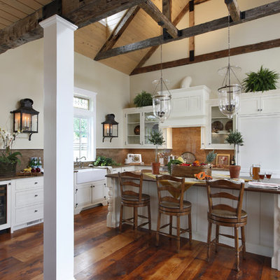 Large farmhouse l-shaped dark wood floor and brown floor kitchen photo in Philadelphia with a farmhouse sink, white cabinets, stone slab backsplash, paneled appliances, beaded inset cabinets, granite countertops, an island and brown countertops