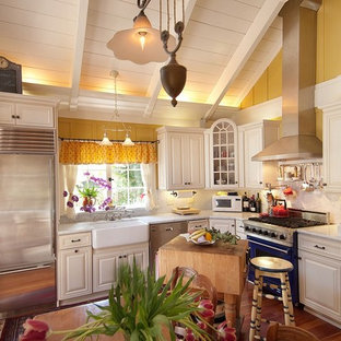 Small traditional kitchen appliance - Example of a small classic l-shaped medium tone wood floor kitchen design in Seattle with colored appliances, a farmhouse sink, beaded inset cabinets, white cabinets, marble countertops, white backsplash, stone slab backsplash and an island
