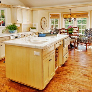 Mid-sized traditional enclosed kitchen ideas - Inspiration for a mid-sized timeless galley medium tone wood floor enclosed kitchen remodel in Seattle with tile countertops, a double-bowl sink, shaker cabinets, light wood cabinets, white backsplash, ceramic backsplash and an island