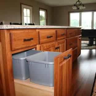 Mittelgroße Klassische Wohnküche in L-Form mit Doppelwaschbecken, profilierten Schrankfronten, dunklen Holzschränken, Granit-Arbeitsplatte, Küchenrückwand in Beige, Rückwand aus Keramikfliesen, Küchengeräten aus Edelstahl, dunklem Holzboden und Kücheninsel in Sonstige