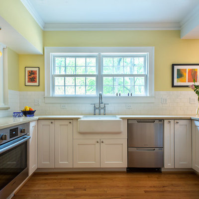 Open concept kitchen - mid-sized traditional u-shaped medium tone wood floor and brown floor open concept kitchen idea in Atlanta with a farmhouse sink, shaker cabinets, white cabinets, white backsplash, subway tile backsplash, stainless steel appliances and a peninsula