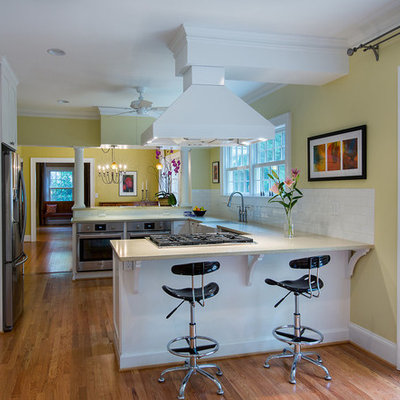 Mid-sized elegant u-shaped medium tone wood floor and brown floor open concept kitchen photo in Atlanta with a farmhouse sink, shaker cabinets, white cabinets, white backsplash, subway tile backsplash, stainless steel appliances and a peninsula