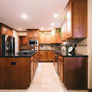 This is an example of a traditional l-shaped eat-in kitchen in Other with an undermount sink, raised-panel cabinets, medium wood cabinets, quartz benchtops, beige splashback, porcelain splashback, stainless steel appliances, porcelain floors, with island, beige floor and black benchtop.