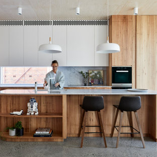 Large contemporary galley kitchen in Melbourne with an undermount sink, flat-panel cabinets, light wood cabinets, grey splashback, panelled appliances, terrazzo floors, with island, grey floor and white benchtop.