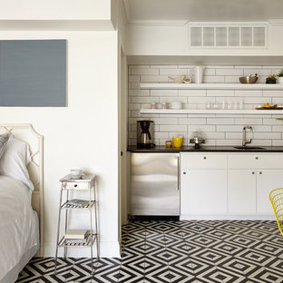 This is an example of a small transitional single-wall kitchen in Nashville with a single-bowl sink, open cabinets, white cabinets, white splashback, subway tile splashback, stainless steel appliances and multi-coloured floor.