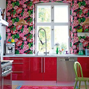 Foto på ett funkis kök, med rostfria vitvaror, röda skåp och släta luckor