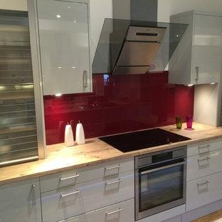 ケンブリッジシャーの中サイズのコンテンポラリースタイルのおしゃれなキッチン (ドロップインシンク、フラットパネル扉のキャビネット、グレーのキャビネット、木材カウンター、赤いキッチンパネル、ガラス板のキッチンパネル、シルバーの調理設備、無垢フローリング) の写真