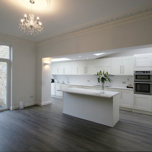 Mid-sized trendy galley eat-in kitchen photo in London with an undermount sink, recessed-panel cabinets, white cabinets, granite countertops, white backsplash, stainless steel appliances and an island