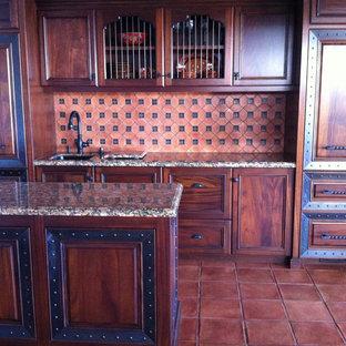 オレンジカウンティの大きい地中海スタイルのおしゃれなキッチン (アンダーカウンターシンク、レイズドパネル扉のキャビネット、中間色木目調キャビネット、御影石カウンター、茶色いキッチンパネル、モザイクタイルのキッチンパネル、シルバーの調理設備、テラコッタタイルの床) の写真