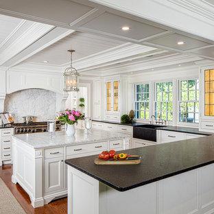 ボストンのビーチスタイルのおしゃれなアイランドキッチン (エプロンフロントシンク、ガラス扉のキャビネット、白いキャビネット、白いキッチンパネル、大理石の床、シルバーの調理設備の、無垢フローリング、オレンジの床) の写真