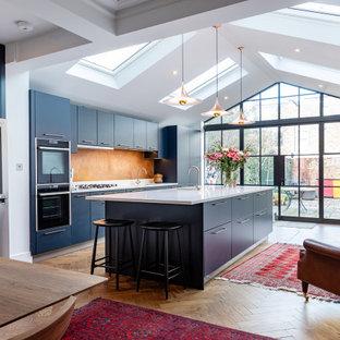 ロンドンの広いコンテンポラリースタイルのおしゃれなキッチン (フラットパネル扉のキャビネット、アンダーカウンターシンク、青いキャビネット、オレンジのキッチンパネル、シルバーの調理設備、茶色い床、白いキッチンカウンター) の写真