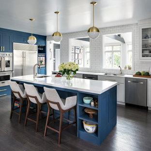 Ispirazione per una grande cucina classica con lavello a doppia vasca, ante in stile shaker, ante blu, top in quarzo composito, paraspruzzi bianco, elettrodomestici in acciaio inossidabile, isola, pavimento marrone, paraspruzzi con piastrelle diamantate e parquet scuro