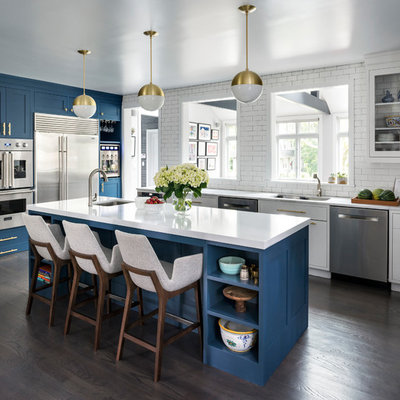 Kitchen - large transitional l-shaped brown floor and dark wood floor kitchen idea in New York with a double-bowl sink, shaker cabinets, blue cabinets, quartz countertops, white backsplash, stainless steel appliances, an island and subway tile backsplash