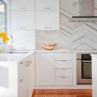 Idee per una cucina minimal di medie dimensioni con lavello sottopiano, ante lisce, ante bianche, top in quarzo composito, paraspruzzi grigio, paraspruzzi con piastrelle in pietra, elettrodomestici in acciaio inossidabile, pavimento in bambù e isola
