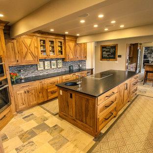 Пример оригинального дизайна: параллельная кухня среднего размера в стиле кантри с обеденным столом, гранитной столешницей, островом, врезной раковиной, фасадами в стиле шейкер, фасадами цвета дерева среднего тона, серым фартуком, фартуком из удлиненной плитки, техникой из нержавеющей стали, полом из известняка и разноцветным полом