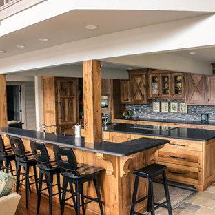 他の地域の中くらいのカントリー風おしゃれなキッチン (御影石カウンター、アンダーカウンターシンク、シェーカースタイル扉のキャビネット、中間色木目調キャビネット、グレーのキッチンパネル、ボーダータイルのキッチンパネル、シルバーの調理設備、ライムストーンの床、マルチカラーの床) の写真