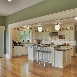 This is an example of a large rural l-shaped open plan kitchen in Detroit with recessed-panel cabinets, white cabinets, beige splashback, a belfast sink, granite worktops, ceramic splashback, integrated appliances, medium hardwood flooring and an island.
