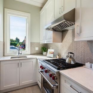バンクーバーの小さいトランジショナルスタイルのおしゃれなキッチン (アンダーカウンターシンク、シェーカースタイル扉のキャビネット、白いキャビネット、クオーツストーンカウンター、ベージュキッチンパネル、モザイクタイルのキッチンパネル、シルバーの調理設備の、磁器タイルの床、アイランドなし、ベージュの床、ベージュのキッチンカウンター) の写真