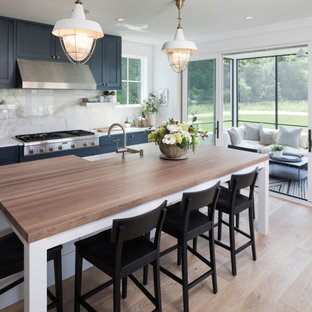 Inspiration for a farmhouse galley light wood floor and beige floor kitchen remodel in Minneapolis with a farmhouse sink, shaker cabinets, blue cabinets, white backsplash, stone slab backsplash, stainless steel appliances, an island and white countertops