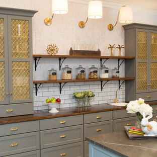 Inspiration for a large transitional u-shaped eat-in kitchen in Chicago with a farmhouse sink, shaker cabinets, grey cabinets, limestone benchtops, white splashback, subway tile splashback, black appliances, porcelain floors, with island and grey floor.