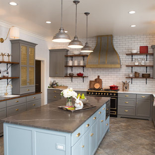 Large transitional separate kitchen in Chicago with a farmhouse sink, shaker cabinets, grey cabinets, limestone benchtops, white splashback, subway tile splashback, black appliances, porcelain floors, with island, grey floor and grey benchtop.