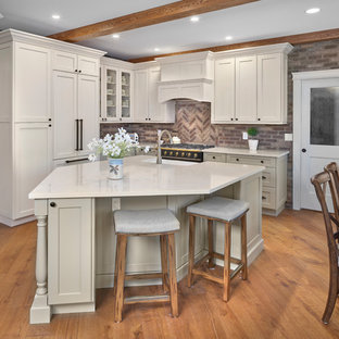Photo of a mid-sized traditional l-shaped eat-in kitchen in Edmonton with a farmhouse sink, recessed-panel cabinets, green cabinets, quartz benchtops, brown splashback, brick splashback, panelled appliances, light hardwood floors, with island, brown floor and beige benchtop.
