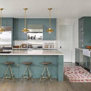 Foto på ett vintage l-kök, med en rustik diskho, luckor med infälld panel, blå skåp, rostfria vitvaror, en köksö, vitt stänkskydd och mörkt trägolv