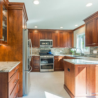 This is an example of a medium sized contemporary u-shaped kitchen/diner in Chicago with a submerged sink, recessed-panel cabinets, medium wood cabinets, granite worktops, brown splashback, glass sheet splashback, stainless steel appliances, ceramic flooring, a breakfast bar and white floors.
