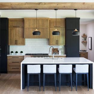 Klassische Wohnküche in L-Form mit Waschbecken, flächenbündigen Schrankfronten, schwarzen Schränken, Quarzwerkstein-Arbeitsplatte, Küchenrückwand in Weiß, Rückwand aus Porzellanfliesen, schwarzen Elektrogeräten, Kücheninsel, weißer Arbeitsplatte, braunem Holzboden und braunem Boden in Minneapolis
