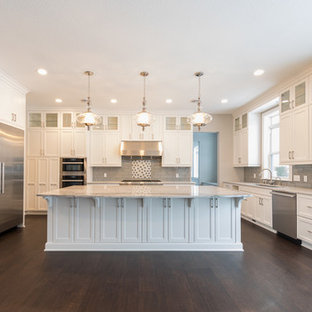 This is an example of an expansive traditional u-shaped kitchen/diner in Minneapolis with a triple-bowl sink, recessed-panel cabinets, white cabinets, granite worktops, grey splashback, glass tiled splashback, stainless steel appliances, dark hardwood flooring, an island and brown floors.
