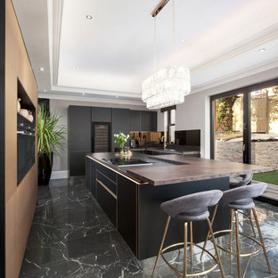 This is an example of an expansive contemporary u-shaped kitchen in Miami with an undermount sink, flat-panel cabinets, black cabinets, wood benchtops, panelled appliances, porcelain floors, with island, black floor and brown benchtop.