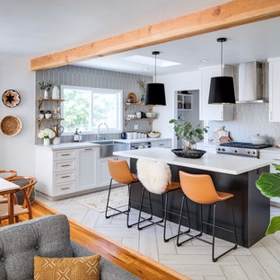 This is an example of a mid-sized transitional l-shaped eat-in kitchen in San Diego with a farmhouse sink, shaker cabinets, black cabinets, quartz benchtops, grey splashback, ceramic splashback, stainless steel appliances, porcelain floors, with island and white benchtop.