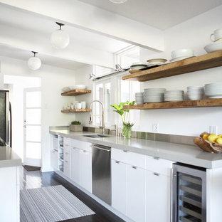 Ispirazione per una cucina parallela contemporanea con lavello sottopiano, ante lisce, ante bianche, elettrodomestici in acciaio inossidabile, parquet scuro, pavimento nero, top grigio e isola