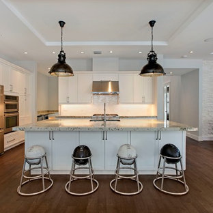 Large transitional l-shaped eat-in kitchen in Miami with shaker cabinets, white cabinets, white splashback, stainless steel appliances, an undermount sink, recycled glass benchtops, subway tile splashback, dark hardwood floors and with island.