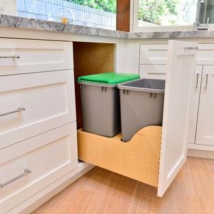 Bild på ett mellanstort funkis kök, med skåp i shakerstil, vita skåp, bänkskiva i kvartsit, vitt stänkskydd, stänkskydd i stenkakel, rostfria vitvaror och mellanmörkt trägolv