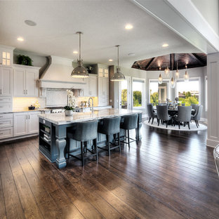 Traditional l-shaped kitchen/diner in Kansas City with a belfast sink, shaker cabinets, white cabinets, white splashback, integrated appliances, dark hardwood flooring, an island, brown floors and beige worktops.