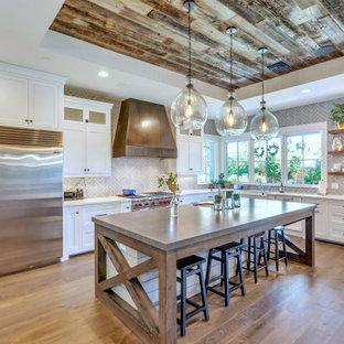 Idéer för ett lantligt vit l-kök, med en rustik diskho, skåp i shakerstil, vita skåp, grått stänkskydd, stänkskydd i tunnelbanekakel, rostfria vitvaror, mellanmörkt trägolv, en köksö och brunt golv