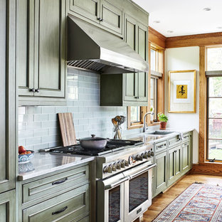 Mid-sized craftsman open concept kitchen appliance - Open concept kitchen - mid-sized craftsman single-wall medium tone wood floor and brown floor open concept kitchen idea in DC Metro with an undermount sink, recessed-panel cabinets, green cabinets, quartz countertops, green backsplash, glass tile backsplash, paneled appliances, an island and gray countertops