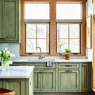 Immagine di una cucina american style di medie dimensioni con lavello sottopiano, ante con riquadro incassato, ante verdi, top in quarzo composito, paraspruzzi verde, paraspruzzi con piastrelle di vetro, elettrodomestici da incasso, pavimento in legno massello medio, isola, pavimento marrone e top grigio