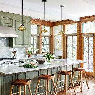 Foto di una cucina stile americano di medie dimensioni con lavello sottopiano, ante con riquadro incassato, ante verdi, top in quarzo composito, paraspruzzi verde, paraspruzzi con piastrelle di vetro, elettrodomestici da incasso, pavimento in legno massello medio, isola, pavimento marrone e top grigio