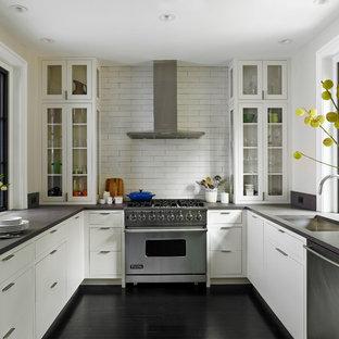 Inredning av ett klassiskt avskilt u-kök, med en undermonterad diskho, luckor med glaspanel, vita skåp, vitt stänkskydd, stänkskydd i tunnelbanekakel, rostfria vitvaror och svart golv