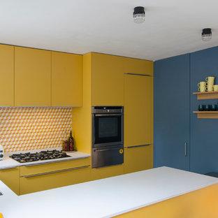 Offene, Kleine Moderne Küche in U-Form mit integriertem Waschbecken, flächenbündigen Schrankfronten, gelben Schränken, Quarzit-Arbeitsplatte, bunter Rückwand, Rückwand aus Zementfliesen, Elektrogeräten mit Frontblende, dunklem Holzboden und Halbinsel in London